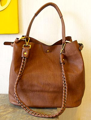 A classic bag in brown leather with a braided handle